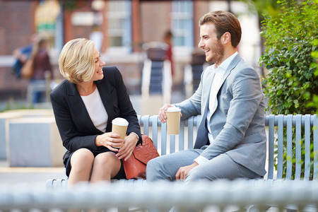 Business Couple On Park Bench With Coffee