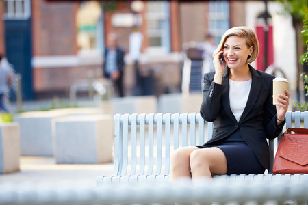 Businesswoman On Park Bench With Coffee Using Mobile Phone photo