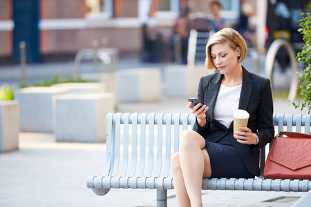 woman on cell phone: Businesswoman On Park Bench With Coffee Using Mobile Phone