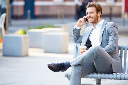 携帯電話を使用してコーヒーを飲みながら公園のベンチで実業家