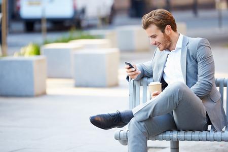 EMPRESARIO: El hombre de negocios en banco de parque con café usando el teléfono móvil Foto de archivo