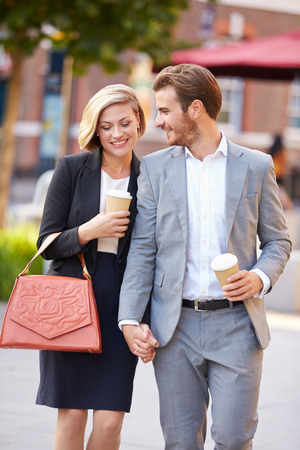 Business Couple Walking Through Park With Takeaway Coffee photo
