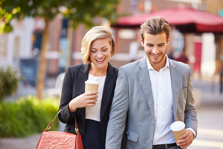 man drinking coffee: Business Couple Walking Through Park With Takeaway Coffee