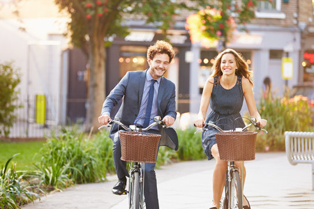 Businesswoman And Businessman Riding Bike Through City Park Stock Photo