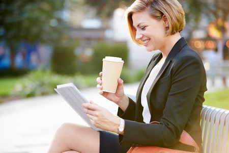 Businesswoman On Park Bench With Coffee Using Digital Tablet photo