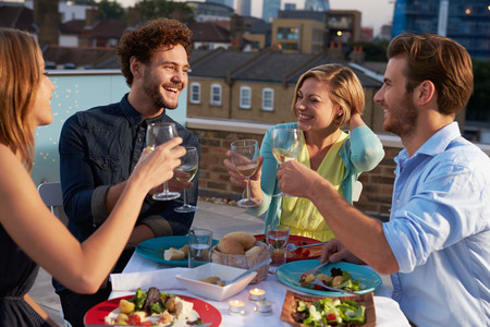 Group Of Friends Eating Meal On Rooftop Terrace photo
