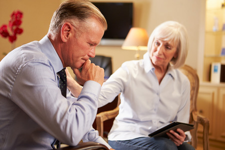 mental health problems: Man Talking To Female Counsellor Using Digital Tablet Stock Photo