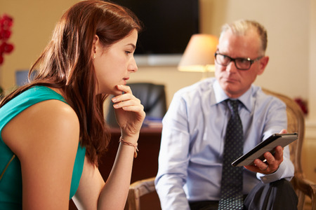 counsellor: Young Woman Talking To Male Counsellor Using Digital Tablet