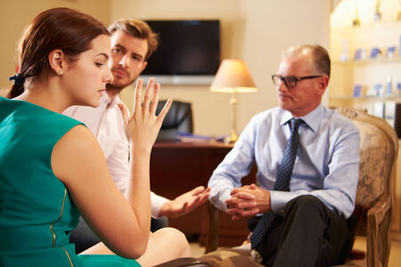 counsellor: Young Couple Talking To Male Counsellor Stock Photo