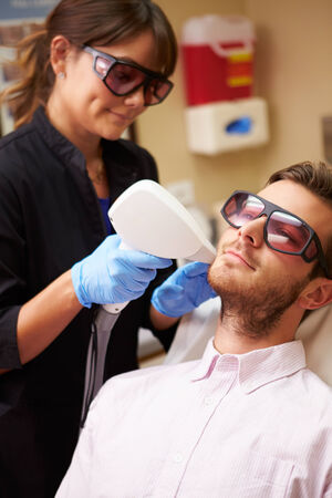 Man Having Laser Treatment At Beauty Clinic photo