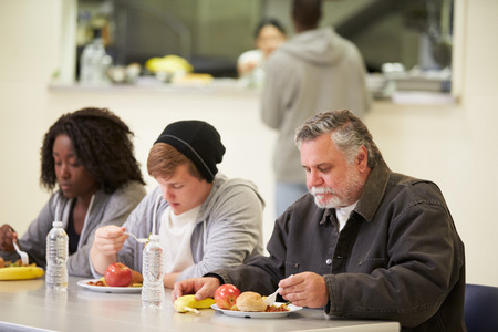 People Sitting At Table Eating Food In Homeless Shelter Stockfoto
