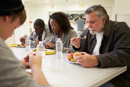 ホームレスのシェルターで食事のテーブルに座って人々
