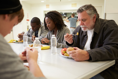 eat: People Sitting At Table Eating Food In Homeless Shelter Stock Photo