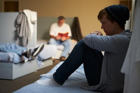 Hombres Acostado de Camas En Homeless Shelter