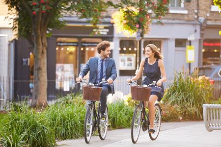 cities: Businesswoman And Businessman Riding Bike Through City Park Stock Photo