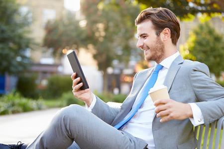 Geschäftsmann auf Park-Bank Mit Kaffee mit digitalen Tablet Standard-Bild