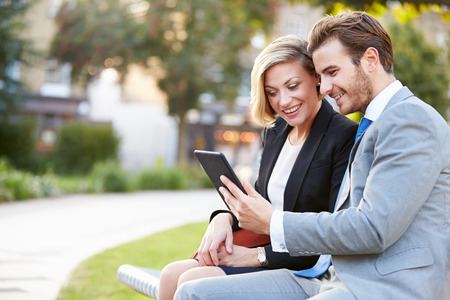 Business Couple Using Digital Tablet On Park Bench photo