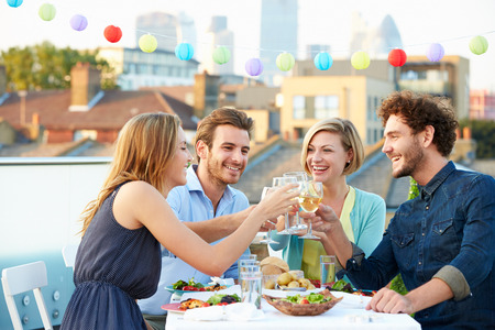 friend: Group Of Friends Eating Meal On Rooftop Terrace Stock Photo