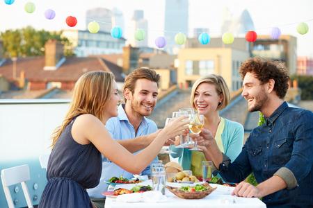 comiendo: Grupo de Amigos que comen la comida en la terraza de la azotea Foto de archivo