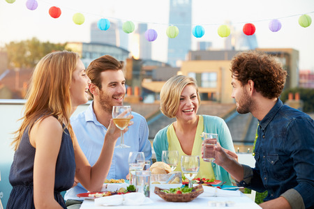 food on white: Group Of Friends Eating Meal On Rooftop Terrace Stock Photo