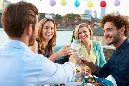 drink: Group Of Friends Eating Meal On Rooftop Terrace Stock Photo
