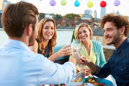 amigos hablando: Grupo de Amigos que comen la comida en la terraza de la azotea Foto de archivo