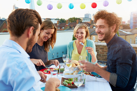 rooftop: Group Of Friends Eating Meal On Rooftop Terrace Stock Photo