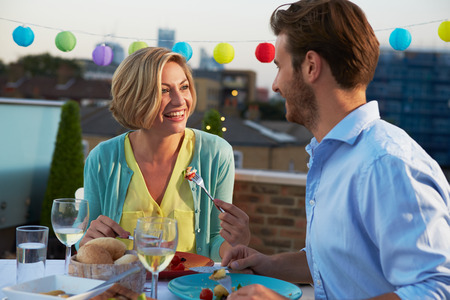 Couple Eating Evening Meal On Rooftop Terrace photo