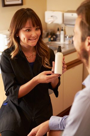 advising: Beautician Advising Male Client On Beauty Products