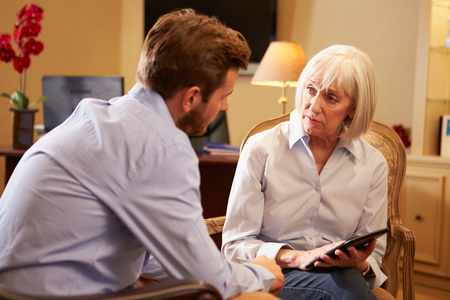 counsellor: Young Man Talking To Counsellor Using Digital Tablet Stock Photo