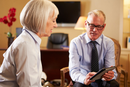Woman Talking To Male Counsellor Using Digital Tablet photo