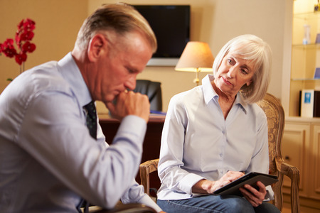 counsellor: Man Talking To Female Counsellor Using Digital Tablet Stock Photo