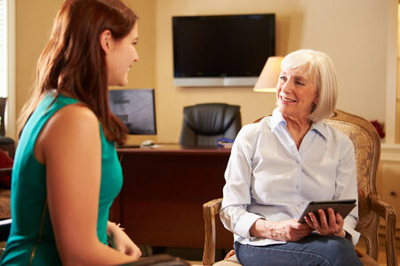 counsellor: Young Woman Talking To Counsellor Using Digital Tablet Stock Photo
