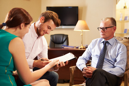 Young Couple Talking To Financial Advisor In Office photo