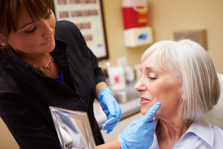 botox: Female Client Looking In Mirror After Botox Treatment