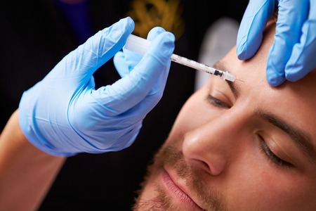 plastic glove: Man Having Botox Treatment At Beauty Clinic