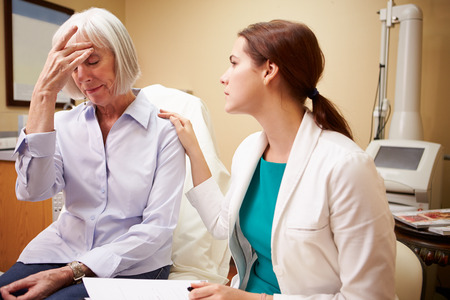 reassurance: Doctor In Consultation With Senior Concerned Female Patient