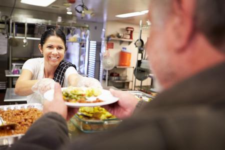 clochard: Cucina che serve cibo In Homeless Shelter