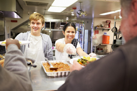 Staff Serving Food In Homeless Shelter Kitchen Stockfoto