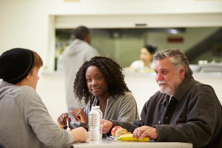 Mensen zitten aan tafel te eten Voedsel In daklozenopvang Stockfoto