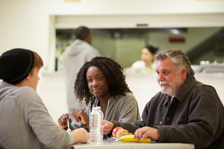 people eating: People Sitting At Table Eating Food In Homeless Shelter Stock Photo