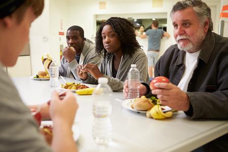comidas: La gente sentada a la mesa comiendo los alimentos en un refugio para personas sin hogar