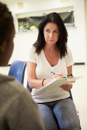 dos personas hablando: Mujer que habla con el consejero que tome notas