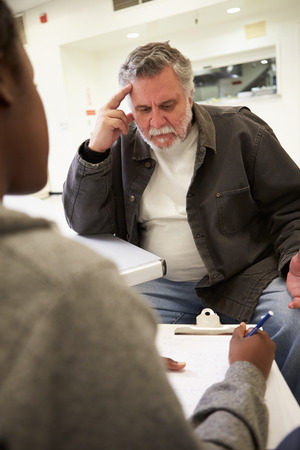 counsellor: Man Talking To Counsellor Who Takes Notes Stock Photo