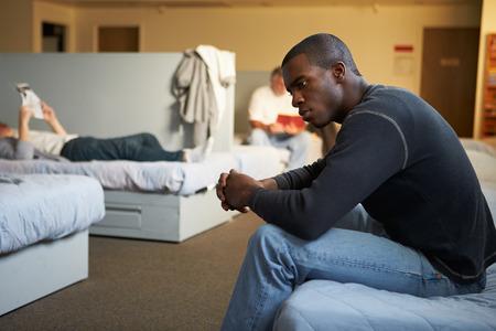 ホームレスの避難所のベッドの上に座っている男性
