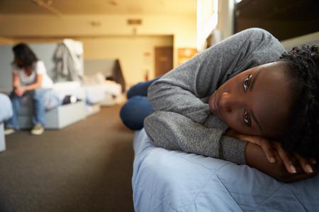 Women Lying On Beds In Homeless Shelter