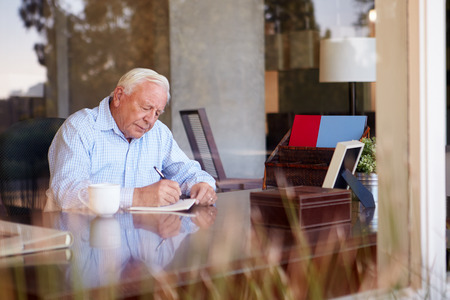 writing on glass: Senior Man Writing Memoirs In Book Sitting At Desk Stock Photo