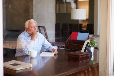 escribiendo: Hombre mayor Escribir Memorias En el Libro Sentado En El Escritorio Foto de archivo