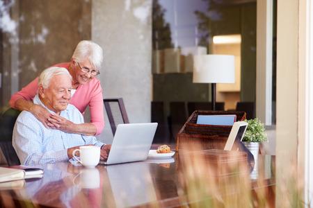 自宅の机の上のノート パソコンを使用してシニア カップル