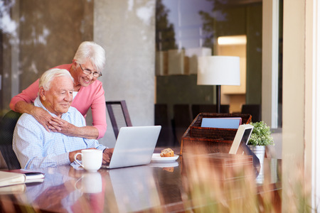 male senior adults: Senior Couple Using Laptop On Desk At Home
